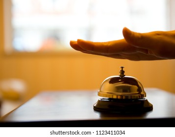 Hand ringing in service bell on wooden table.