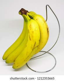 A hand of ripe yellow bananas on a chrome stand.