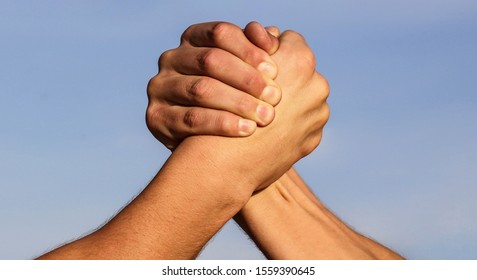Hand, rivalry, vs, challenge, strength comparison. Two muscular hands. Rivalry concept. Two men arm wrestling. Arms wrestling. Friendly handshake, friends greeting, teamwork. Closep up, macro.