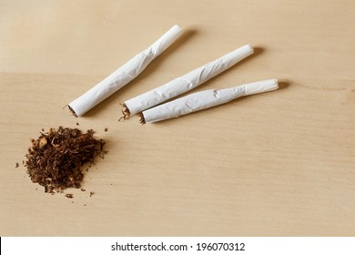 Hand rolled cigarettes and tobacco on a wooden table