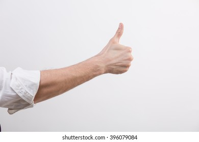 Hand with rolled sleeve in a studio with thumb up
