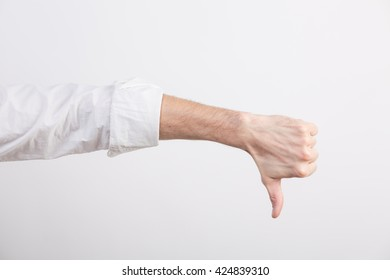 Hand with rolled sleeve with thumb down in a studio