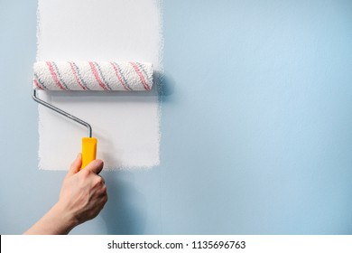 A hand with a roller paints the wall with white paint