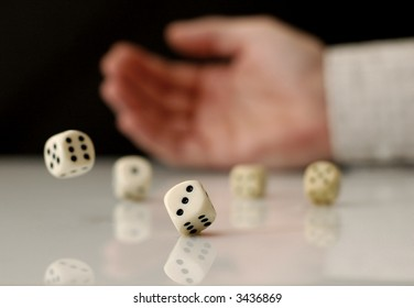 Hand rolling dices on white table, with reflection. Shallow depth of field.