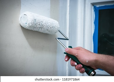 Hand rolling white house paint/primer on prepped wall, using hand roller.