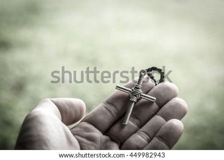 Hand with a rosary against gray background, religious concept.process in vintage color tone