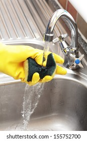 Hand in a rubber glove holding a cleaning sponge under a running tap in a stainless steel sink