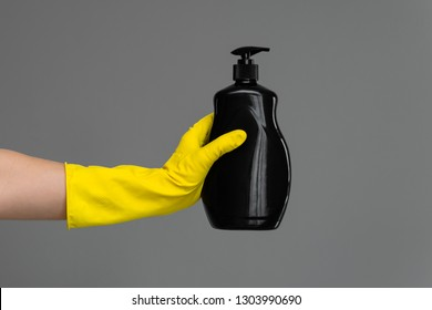 A hand in a rubber glove holds a bottle of dishwashing detergent on a neutral background. The concept of bright spring, spring cleaning.