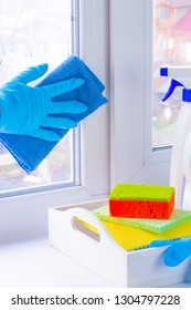 A hand in rubber glove washes a window with a rag. Spring cleaning. Window cleaning using bottle cleaners. On the windowsill is a white tray and detergent, washcloths. Outside the city, blurry. Vertic