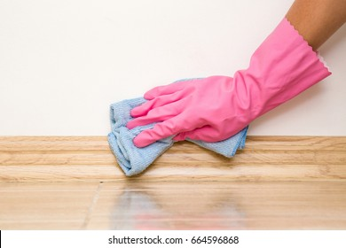 Hand in rubber protective glove cleaning baseboard on the floor from dust with microfiber rag at the wall. Early spring cleaning or regular clean up. Maid cleans house.
