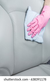 Hand in rubber protective glove with cloth cleaning a car interior's leather seats. Early spring professionally chemical cleaning or regular clean up.