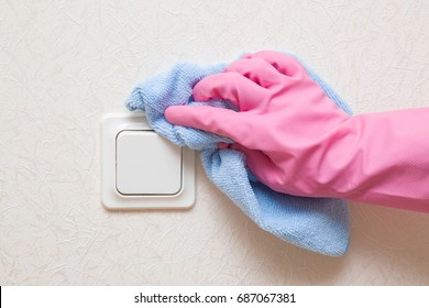 Hand in rubber protective glove with dry microfiber cloth wiping a light switch at the wall from dust. Early spring cleaning or regular clean up. Maid cleans house.