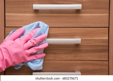 Hand in rubber protective glove with microfiber rag cleaning a cupboard in the room. Early spring cleaning or regular clean up. Maid cleans house.