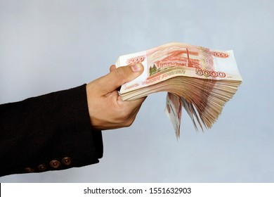 Hand with Russian rubles on a blue background, bills five thousand rubles, money fan in hand. a large wad of money with a million rubles in the hand of a successful young man.