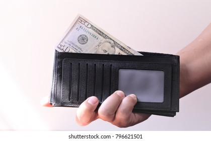 Hand 's holding black leather wallet with US Dollar Banknote and Euro money., isolated on white background with clipping path.