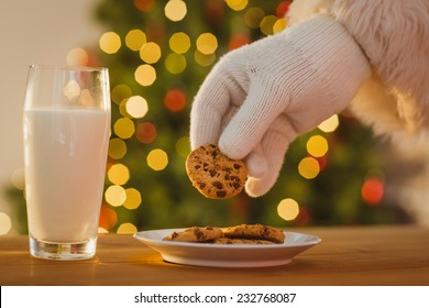 Hand of santa claus picking cookie on the table at home