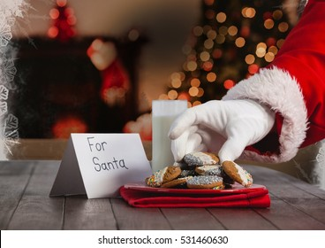 Hand of santa claus putting Christmas cookies on table