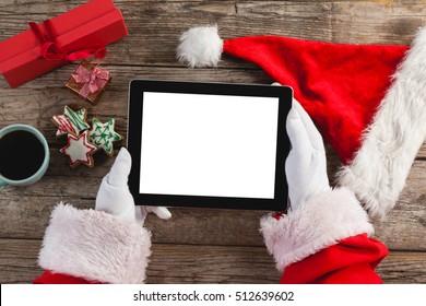 Hand of santa claus using digital tablet on wooden plank