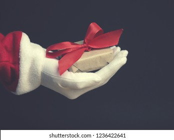 Hand of Santa with gift box on a dark background, modern flat tone stylized Christmas concept