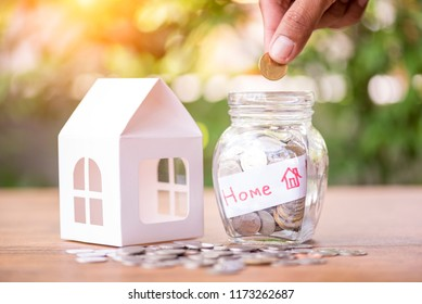 Hand saving money in the glass jar for buying new home, personal loan and deposit concept
