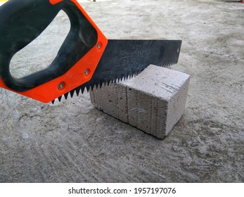 a hand saw cutting a white limestone