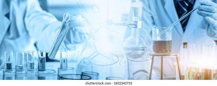hand of scientist holding flask and pouring sample to test tube in chemical laboratory background, science laboratory research and development concept