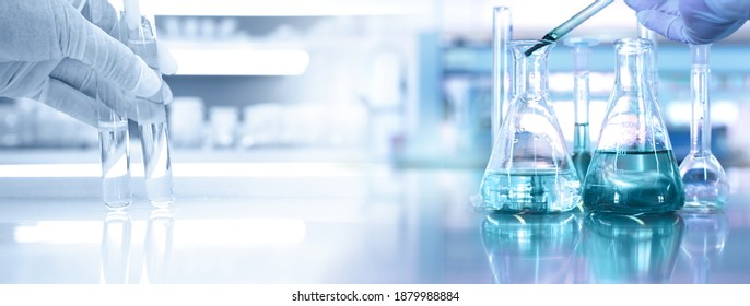 hand of scientist with test tube and flask in medical chemistry lab blue banner background - Shutterstock ID 1879988884