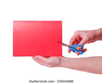 Hand with scissors cut a red sheet of paper on a white background. Isolated on white. Place for text.