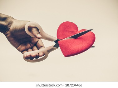hand with scissors trying to cut a red heart