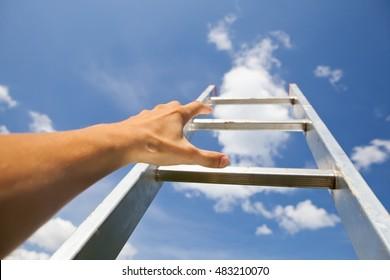 hand scrambling a ladder, blue sky background
