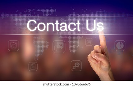 A hand selecting a Contact Us business concept on a clear screen with a colorful blurred background.