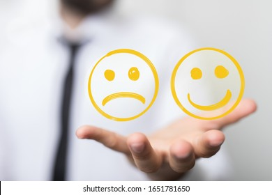 Hand is selecting a happy mood smiley. In front of an empty room