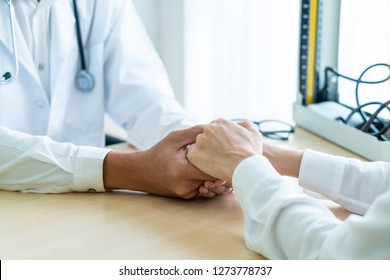 Hand of senior doctor reassuring her female patient