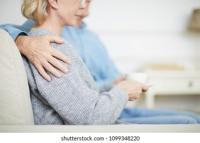 Hand of senior husband on shoulder of his wife during family idyl at home
