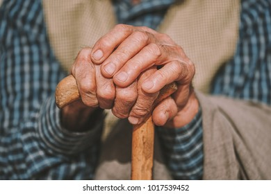 hand of a senior man holding a cane.