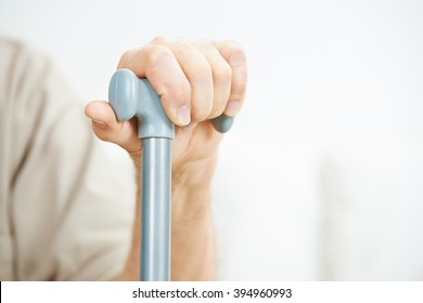 Hand of senior man holding on to a cane