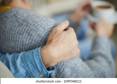 Hand of senior man on his wife shoulder in the moment of home rest