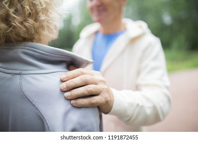 Hand of senior man on shoulder of his wife while comforting and supporting her