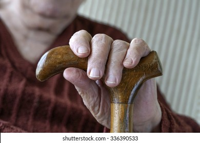 hand of a senior person holding wooden cane