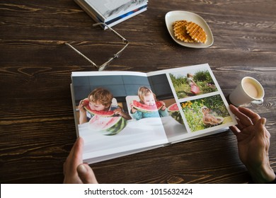 the Hand senior woman holding a family photo album against the background of the a wooden table.