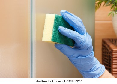 Hand of senior woman in protective gloves using sponge and wiping glass shower door, concept of household duties