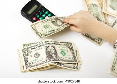 hand separating dollars by type on white background and a black calculator