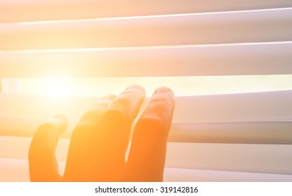 Hand separating slats of venetian blinds with a finger to see through