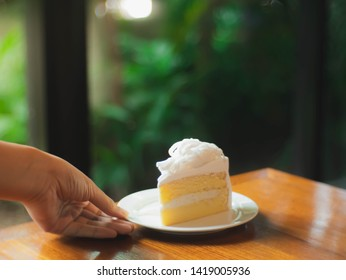 Hand serve a piece of soft cream coconut cake on the wood table in cafe with blur green tree background. Copy space concept.