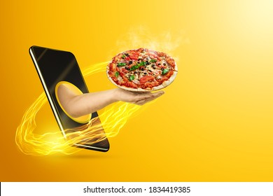 Hand serves pizza via smartphone on yellow background. The concept of food delivery, online ordering, restaurant services at home