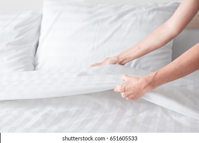 Hand set up white bed in the room