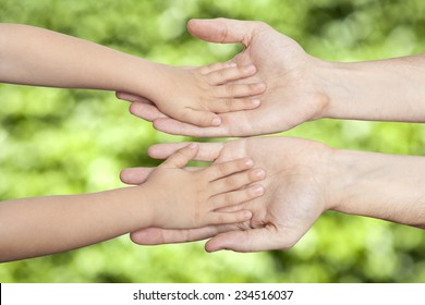 Hand shake of the child and father on green background