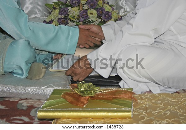 Hand shake during a Malay marriage vow.