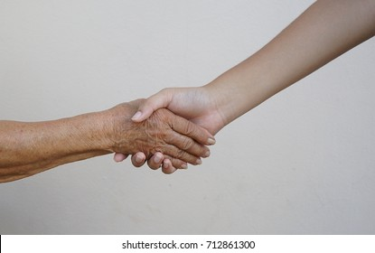 Hand shaking between grandmother, old woman and grandson, teenager. Family, love and companion, aging society concept.
