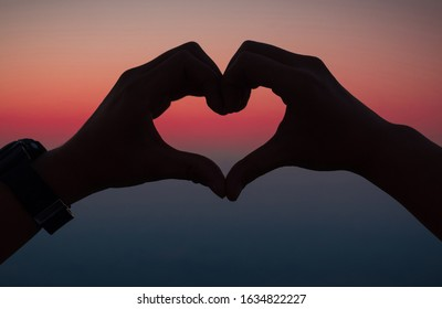 Hand shaped heart with sunset sky. Valentine love and nature concept.